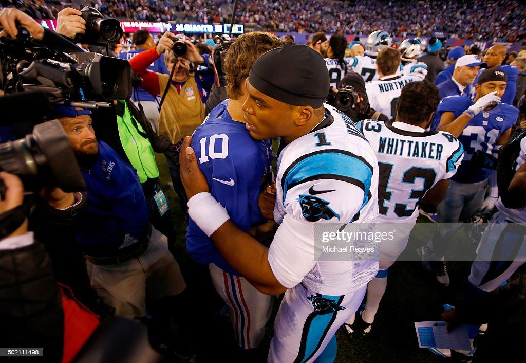 Cam Newton #1 of the Carolina Panthers hugs Eli Manning #10 of the New York Giants after their game at MetLife Stadium on December 20, 2015 in East Rutherford, New Jersey. The Carolina Panthers defeated the New York Giants with a score of 38 to 35.