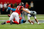 Cam Newton of the Carolina Panthers is sacked by Jonathan Babineaux of the Atlanta Falcons and Kroy Biermann during the first half at the Georgia...
