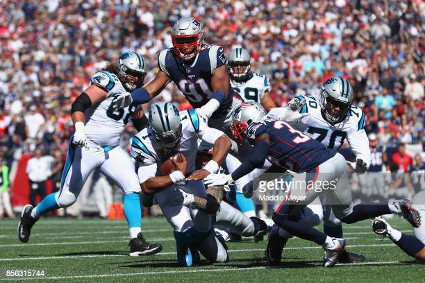 Cam Newton of the Carolina Panthers is tackled by Cassius Marsh of the New England Patriots during the first half at Gillette Stadium on October 1...
