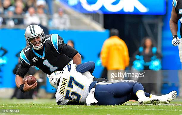 Cam Newton of the Carolina Panthers is tackled by Jatavis Brown of the San Diego Chargers in the 1st quarter during the game at Bank of America...