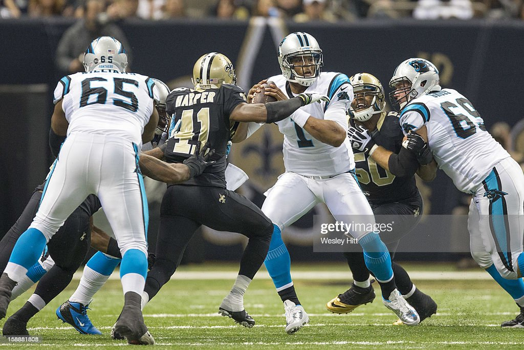 Cam Newton #1 of the Carolina Panthers looks to pass under pressure against the New Orleans Saints at Mercedes-Benz Superdome on December 30, 2012 in New Orleans, Louisiana. The Panthers defeated the Saints 44-38.