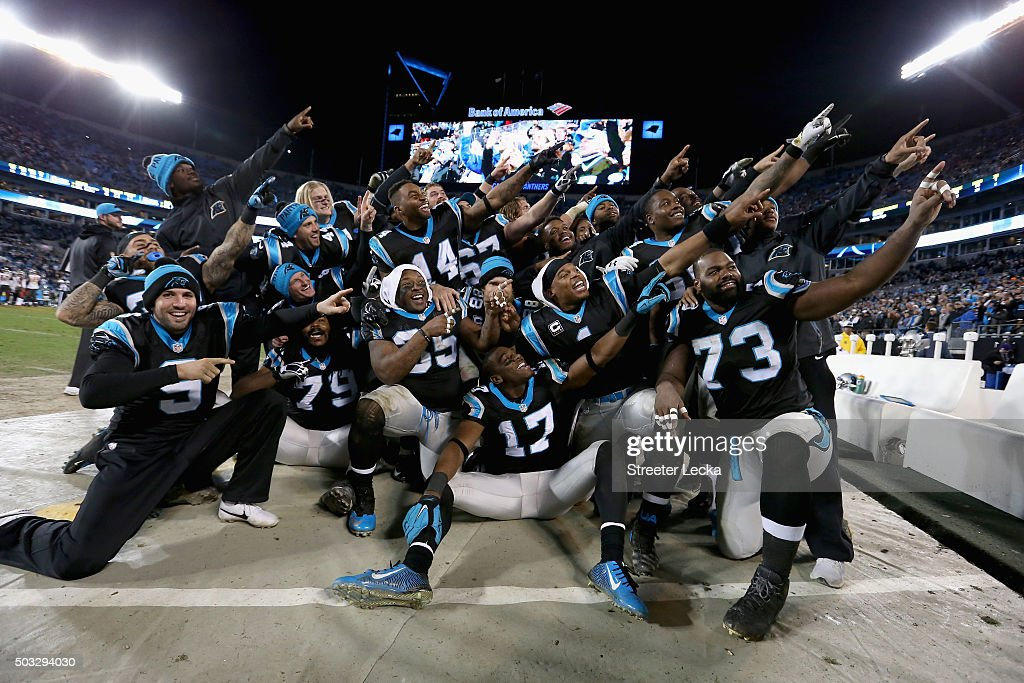 Cam Newton #1 of the Carolina Panthers organizes a team photo in the bench area during their game against the Tampa Bay Buccaneers at Bank of America Stadium on January 3, 2016 in Charlotte, North Carolina. The Panthers won 38-10 to clinch home field advantage for the playoffs