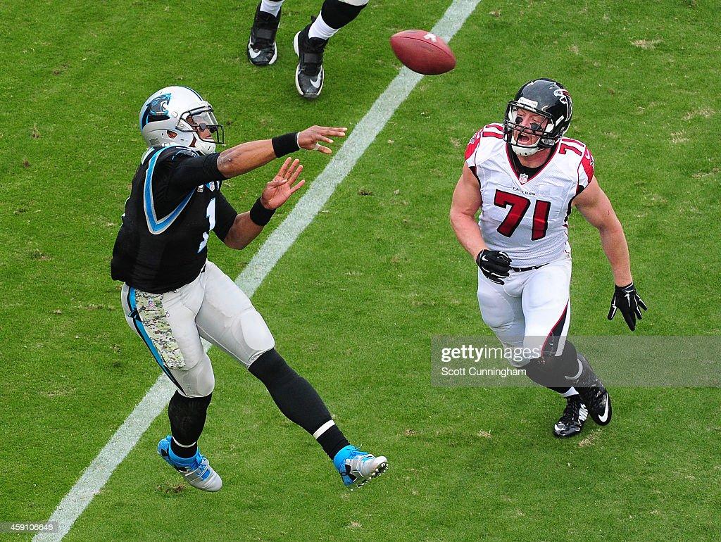 Cam Newton of the Carolina Panthers passes despite pressure from Kroy Biermann of the Atlanta Falcons at Bank Of America Stadium on November 16 2014...
