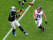 Cam Newton of the Carolina Panthers passes despite pressure from Kroy Biermann of the Atlanta Falcons at Bank Of America Stadium on November 16 2014...