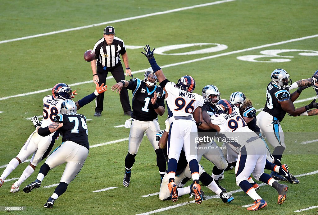 Cam Newton of the Carolina Panthers passes the ball under pressure from Von Miller and Vance Walker of the Denver Broncos during Super Bowl 50 at...