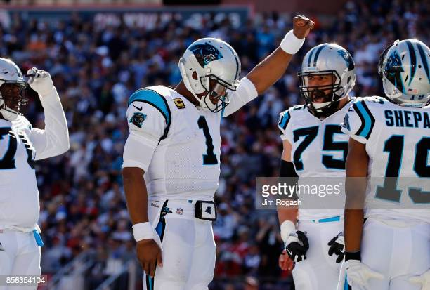 Cam Newton of the Carolina Panthers raises his fist in the end zone after scoring a touchdown during the fourth quarter against the New England...