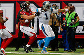 Cam Newton of the Carolina Panthers runs our of bounds against Kroy Biermann of the Atlanta Falcons during the first half at the Georgia Dome on...