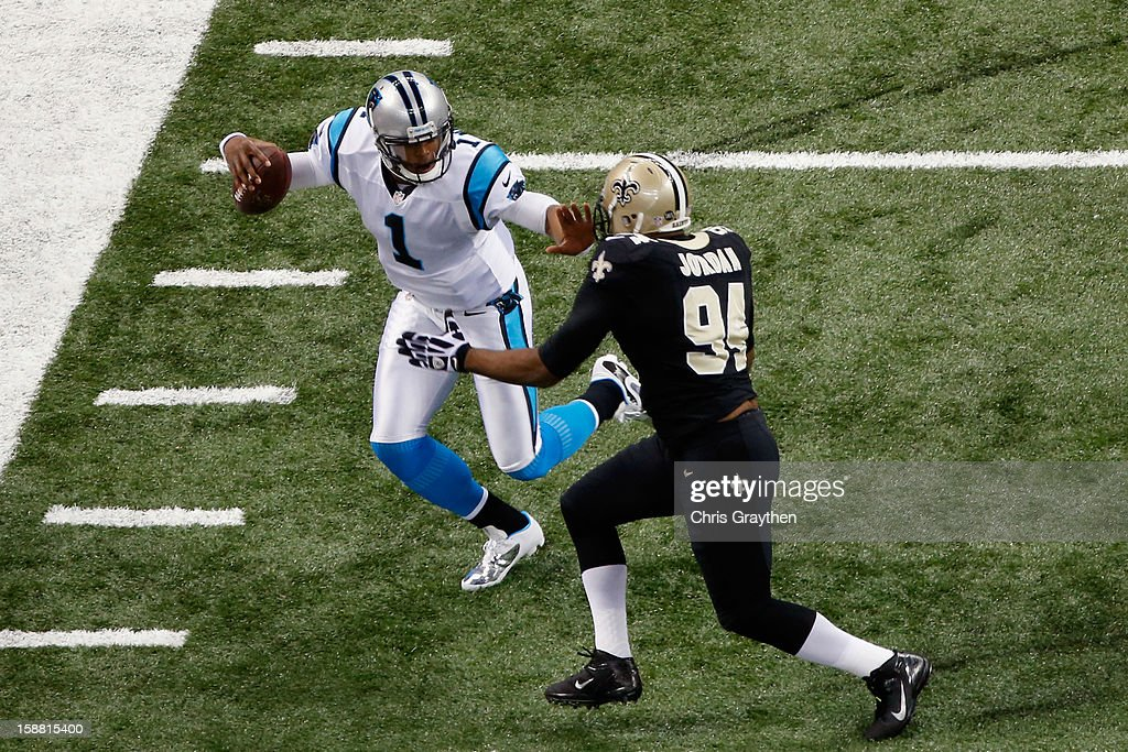 Cam Newton #1 of the Carolina Panthers runs past Cameron Jordan #94 of the New Orleans Saints at the Mercedes-Benz Superdome on December 30, 2012 in New Orleans, Louisiana.