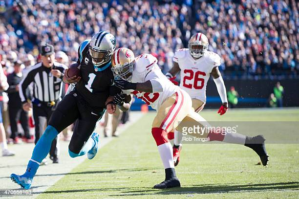 Cam Newton of the Carolina Panthers runs the ball as Patrick Willis of the San Francisco 49ers attempts the tackle during the NFC Divisional Playoff...