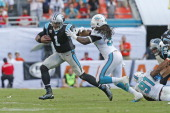 Cam Newton of the Carolina Panthers runs with the ball while being defended by Dannell Ellerbe of the Miami Dolphins on November 24 2013 at Sun Life...