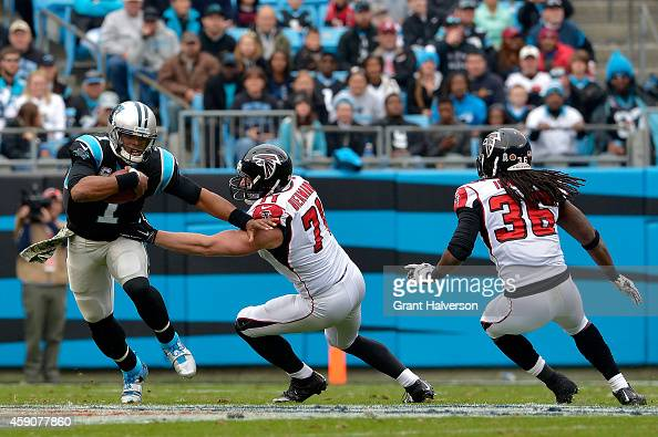 Cam Newton of the Carolina Panthers scrambles from Kroy Biermann and Kemal Ishmael of the Atlanta Falcons in the 1st half during their game at Bank...