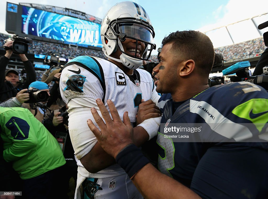 Cam Newton of the Carolina Panthers shakes hands with Russell Wilson of the Seattle Seahawks after the NFC Divisional Playoff Game at Bank of America...