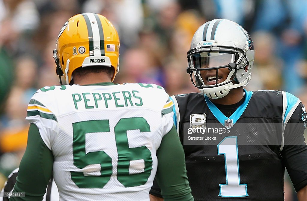 Cam Newton of the Carolina Panthers talks to Julius Peppers of the Green Bay Packers in the 1st half during their game at Bank of America Stadium on...