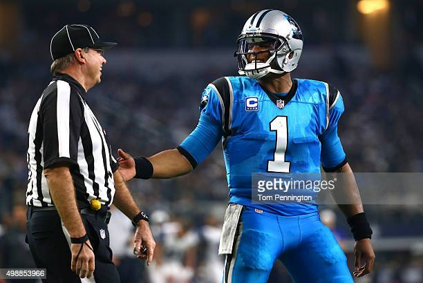 Cam Newton of the Carolina Panthers talks with line judge Mark Steinkerchner as the Panthers take on the Dallas Cowboys in the second half at ATT...