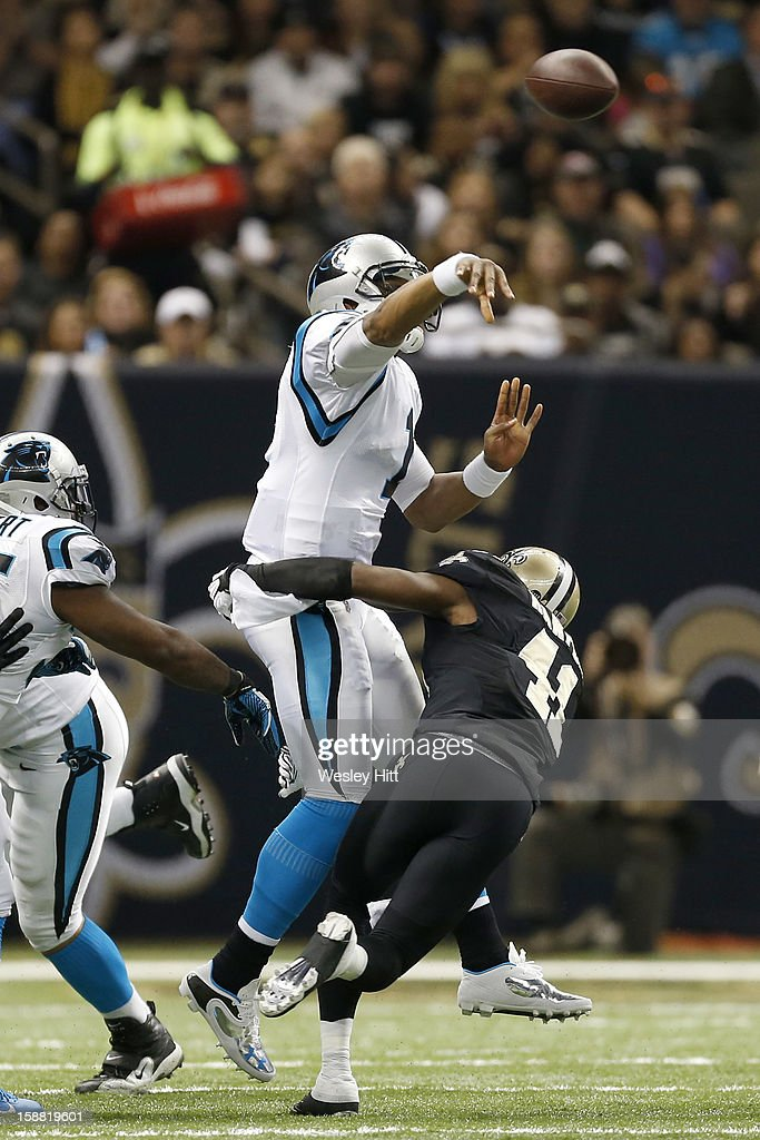Cam Newton #1 of the Carolina Panthers throws a pass under pressure from <a gi-track='captionPersonalityLinkClicked' href=/galleries/search?phrase=Roman+Harper&family=editorial&specificpeople=745620 ng-click='$event.stopPropagation()'>Roman Harper</a> #41 of the New Orleans Saints at Mercedes-Benz Superdome on December 30, 2012 in New Orleans, Louisiana. The Panthers defeated the Saints 44-38.