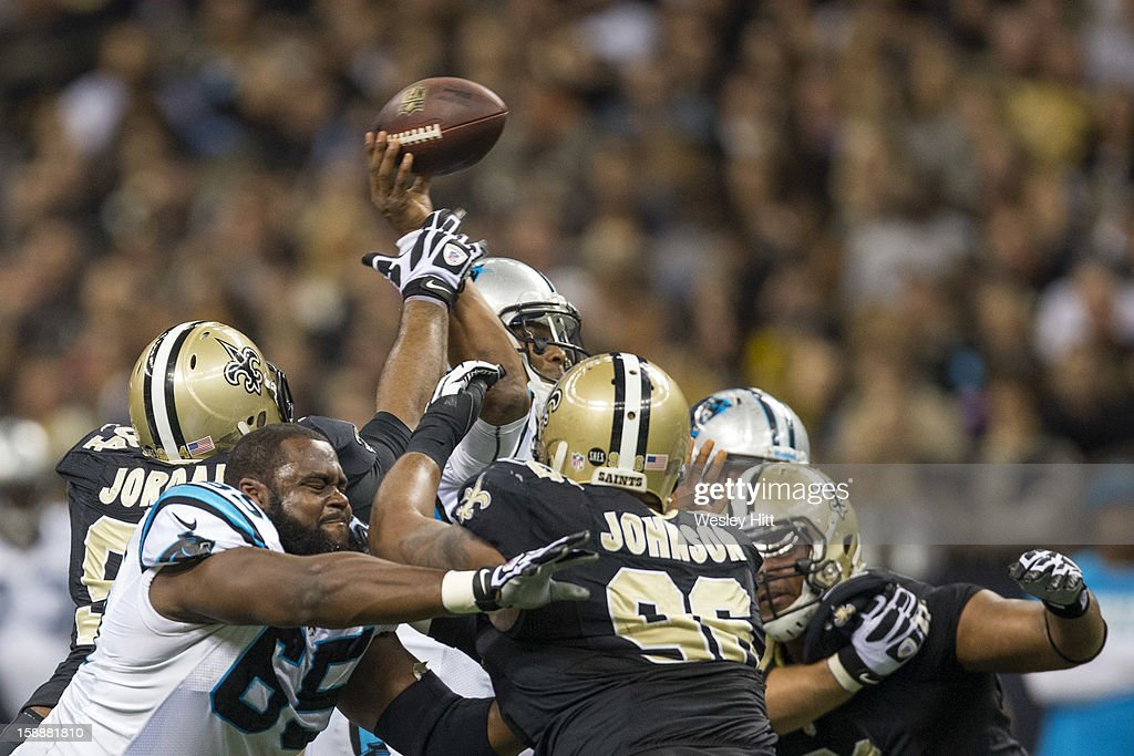 Cam Newton #1 of the Carolina Panthers throws a pass under pressure against the New Orleans Saints at Mercedes-Benz Superdome on December 30, 2012 in New Orleans, Louisiana. The Panthers defeated the Saints 44-38.