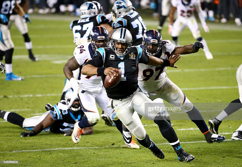 Cam Newton of the Carolina Panthers tries to avoid a tackle by DeMarcus Ware and Malik Jackson of the Denver Broncos in the fourth quarter during...