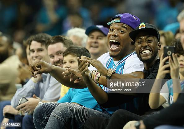 Cam Newton quarterback of the Carolina Panthers reacts as he watches the game between the Cleveland Cavaliers and Charlotte Hornets at Time Warner...