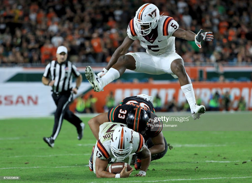 Cam Phillips #5 of the Virginia Tech Hokies jumps over Josh Jackson #17 being tackled by Trent Harris #33 of the Miami Hurricanes during a game at Hard Rock Stadium on November 4, 2017 in Miami Gardens, Florida.