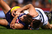 Cam Sutcliffe of the Dockers gets tackled by Tom Hawkins of the Cats during the round 17 AFL match between the Fremantle Dockers and the Geelong Cats...