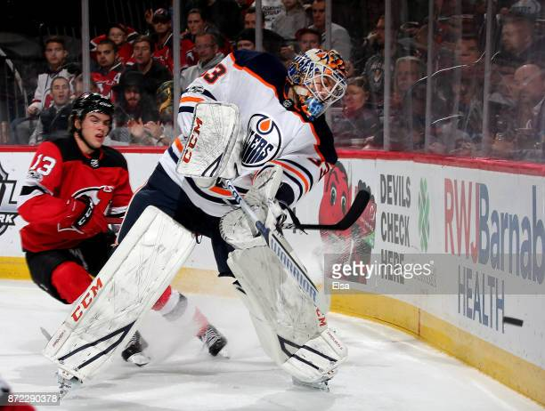 Cam Talbot of the Edmonton Oilers clears the puck as Nico Hischier of the New Jersey Devils skates by in the second period on November 9 2017 at...