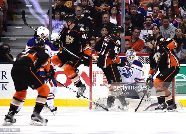 Cam Talbot of the Edmonton Oilers makes a save on a deflected shot in front of Corey Perry and Rickard Rakell of the Anaheim Ducks during the second...