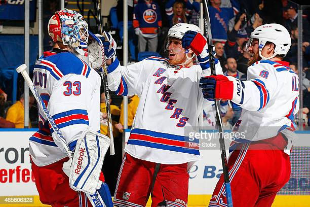 Cam Talbot of the New York Rangers is congratulated by his teammates Marc Staal and Kevin Klein after defeating the New York Islanders at Nassau...