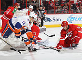 Cam Ward and JohnMichael Liles of the Carolina Hurricanes attempt to defend the net against Josh Bailey of the New York Islanders during their NHL...