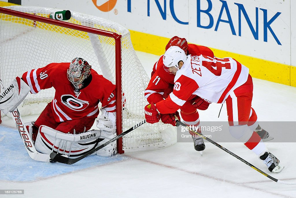 <a gi-track='captionPersonalityLinkClicked' href=/galleries/search?phrase=Cam+Ward&family=editorial&specificpeople=453216 ng-click='$event.stopPropagation()'>Cam Ward</a> #30 and <a gi-track='captionPersonalityLinkClicked' href=/galleries/search?phrase=Jordan+Staal&family=editorial&specificpeople=533044 ng-click='$event.stopPropagation()'>Jordan Staal</a> #11 of the Carolina Hurricanes defend a shot by <a gi-track='captionPersonalityLinkClicked' href=/galleries/search?phrase=Henrik+Zetterberg&family=editorial&specificpeople=201520 ng-click='$event.stopPropagation()'>Henrik Zetterberg</a> #40 of the Detroit Red Wings during play at PNC Arena on October 4, 2013 in Raleigh, North Carolina. The Red Wings defeated the Hurricanes 3-2 in overtime.