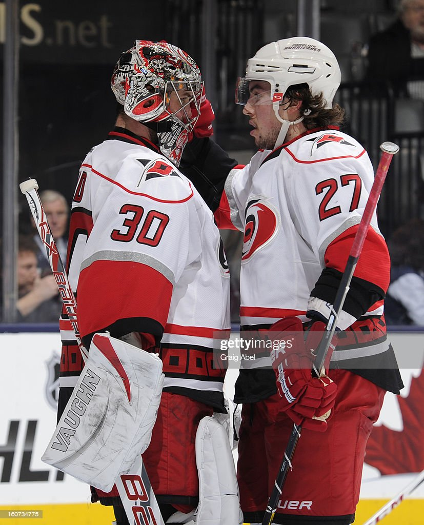 Cam Ward #30 and Justin Faulk #27 of the Carolina Hurricanes celebrate the teams win over the Toronto Maple Leafs during NHL game action February 4, 2013 at the Air Canada Centre in Toronto, Ontario, Canada.