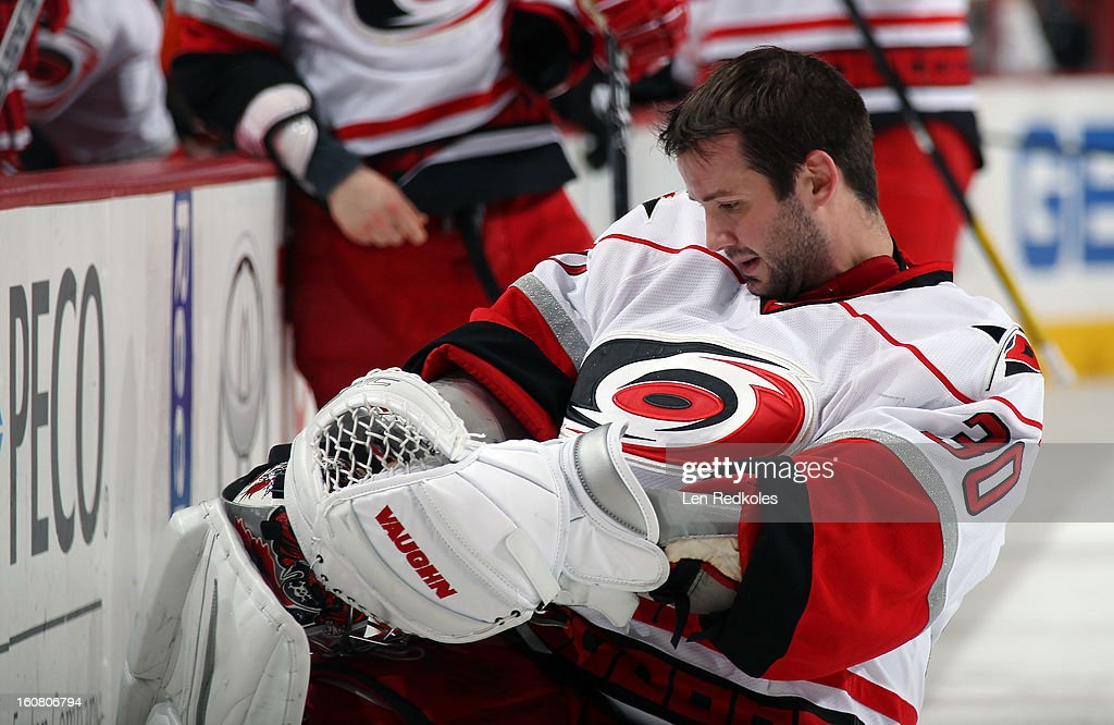 Cam Ward #30 of the Carolina Hurricanes adjust his mask during a stoppage in play against the Philadelphia Flyers on February 2, 2013 at the Wells Fargo Center in Philadelphia, Pennsylvania.