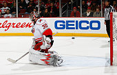 Cam Ward of the Carolina Hurricanes cannot stop the puck as Mattias Tedenby of the New Jersey Devils scores the game winning goal in overtime during...