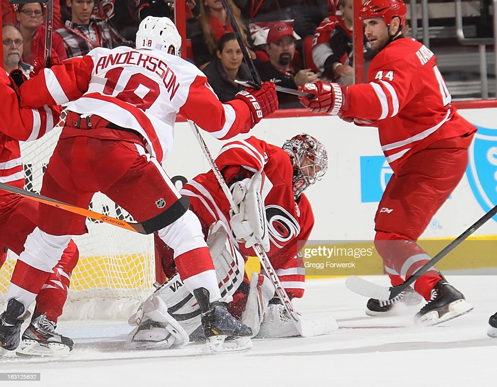 <a gi-track='captionPersonalityLinkClicked' href=/galleries/search?phrase=Cam+Ward&family=editorial&specificpeople=453216 ng-click='$event.stopPropagation()'>Cam Ward</a> #30 of the Carolina Hurricanes covers up the puck as teammate <a gi-track='captionPersonalityLinkClicked' href=/galleries/search?phrase=Jay+Harrison&family=editorial&specificpeople=714374 ng-click='$event.stopPropagation()'>Jay Harrison</a> #44 battles with Joakim Andersson #18 of the Detroit Red Wings during an NHL game on October 4, 2013 in the home opener at PNC Arena in Raleigh, North Carolina.