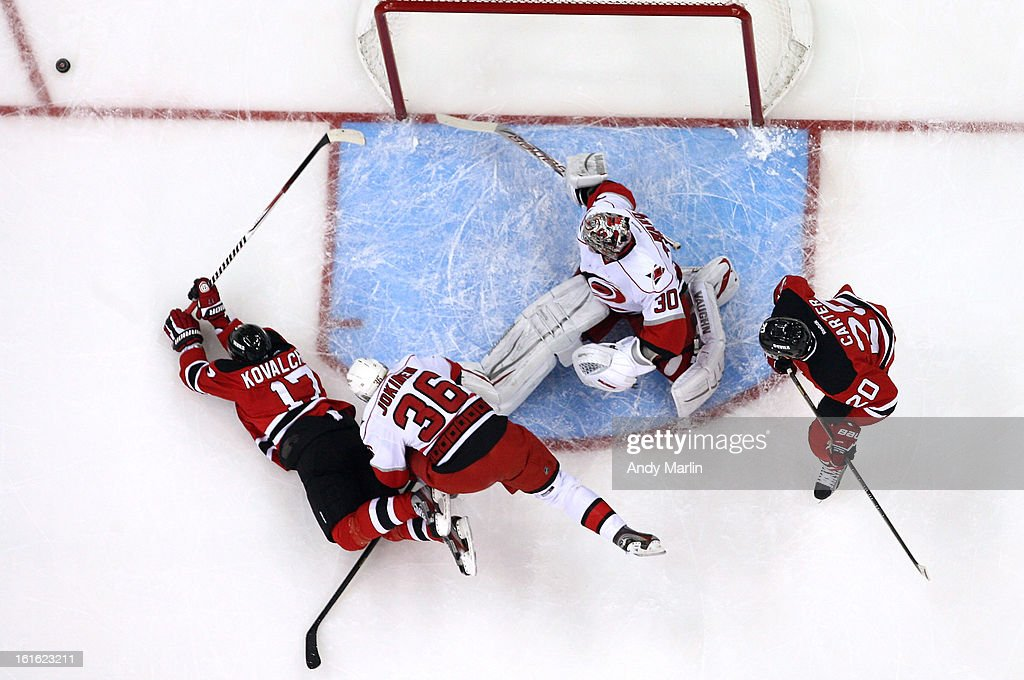 Cam Ward #30 of the Carolina Hurricanes defends his net as Jussi Jokinen #36 knocks down Ilya Kovalchuk #17 of the New Jersey Devils during the game at the Prudential Center on February 12, 2013 in Newark, New Jersey. The Hurricanes defeated the Devils 4-2.