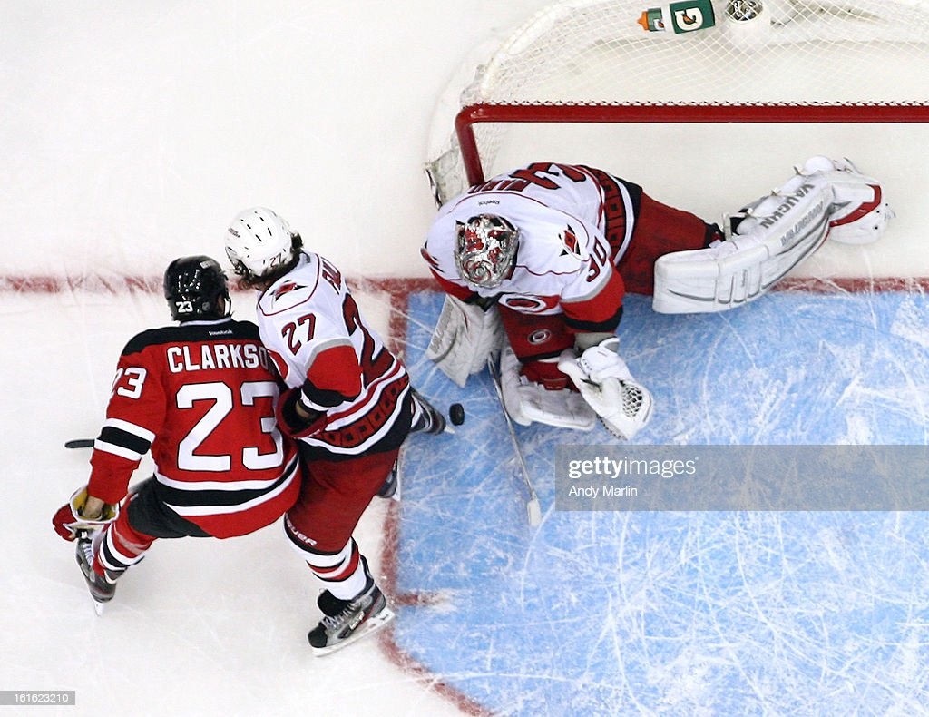 Cam Ward #30 of the Carolina Hurricanes defends his net as Justin Faulk #27 checks David Clarkson #23 of the New Jersey Devils during the game at the Prudential Center on February 12, 2013 in Newark, New Jersey. The Hurricanes defeated the Devils 4-2. Photo by Andy Marlin/NHLI via Getty Images)