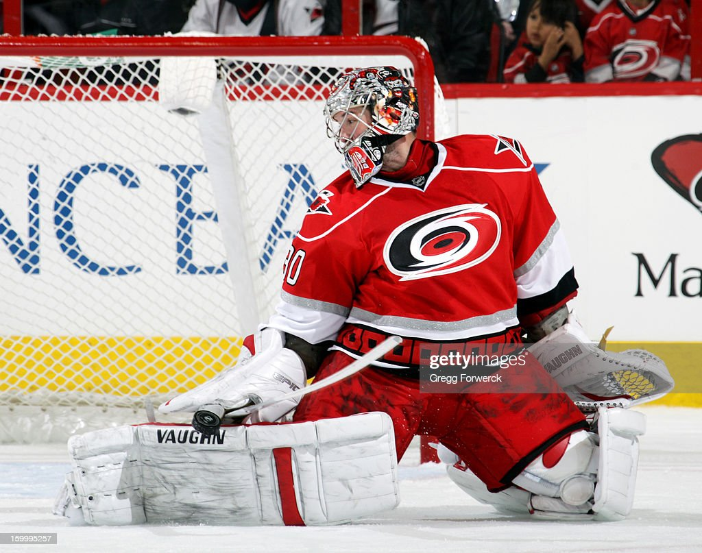 Cam Ward #30 of the Carolina Hurricanes deflects a shot from the Buffalo Sabres during their NHL game at PNC Arena on January 24, 2013.