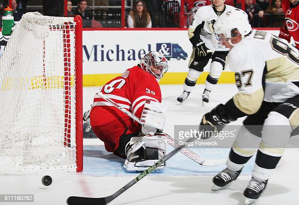 Cam Ward of the Carolina Hurricanes deflects a shot on goal as Sidney Crosby of the Pittsburgh Penguins attempts to settle the puck during an NHL...