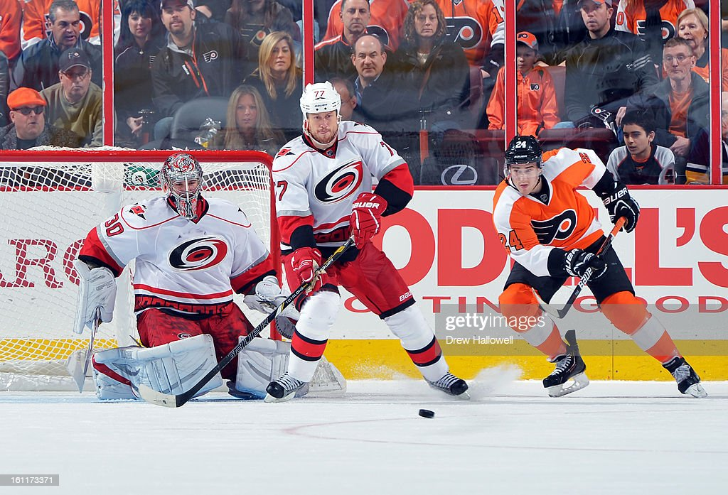 Cam Ward #30 of the Carolina Hurricanes drops to make a save behind teammate Joe Corvo #77 and Matt Read #24 of the Philadelphia Flyers at the Wells Fargo Center on February 9, 2013 in Philadelphia, Pennsylvania. The Flyers won 4-3 in overtime.