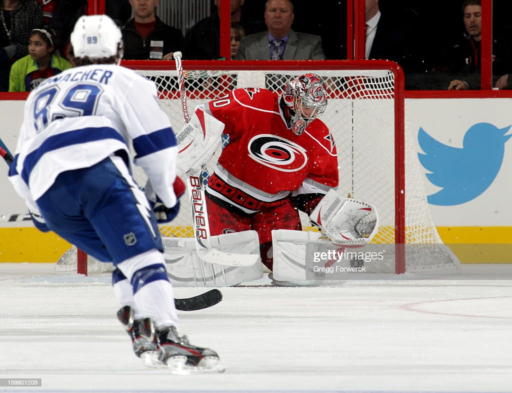 Cam Ward #30 of the Carolina Hurricanes gets a pad on the puck to make a save as Cory Conacher #89 of the Tampa Bay Lightning skates to the crease during an NHL game on January 22, 2013 at PNC Arena in Raleigh, North Carolina.