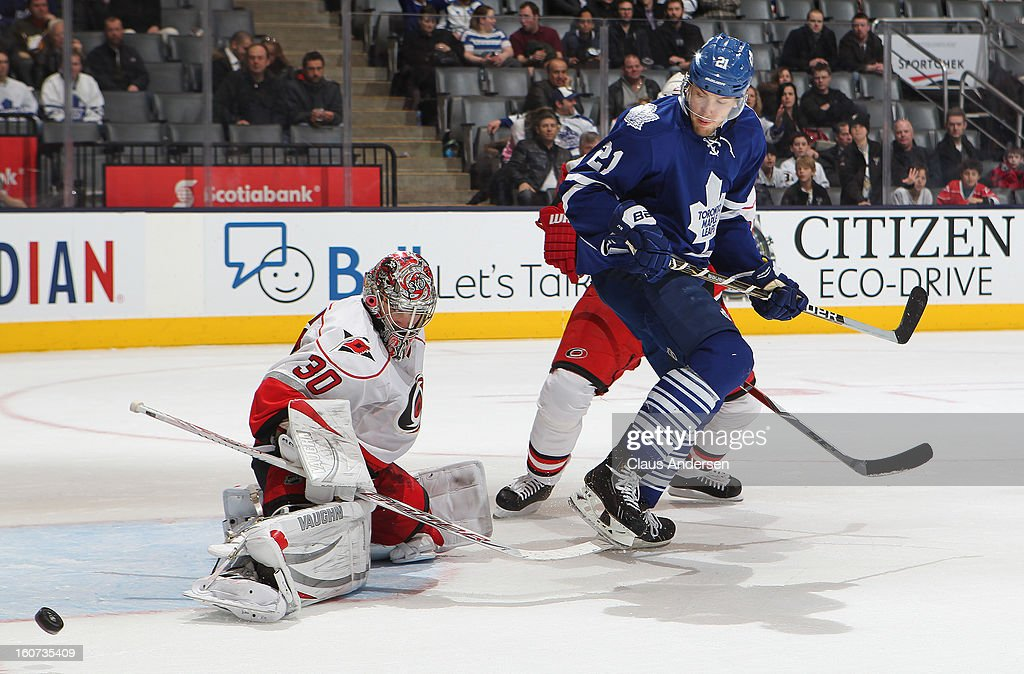 Cam Ward #30 of the Carolina Hurricanes gets a piece of a shot with James van Riemsdyk #21 of the Toronto Maple Leafs standing on his doorstep in a game on February 4, 2013 at the Air Canada Centre in Toronto, Canada. The Hurricanes defeated the Leafs 4-1.