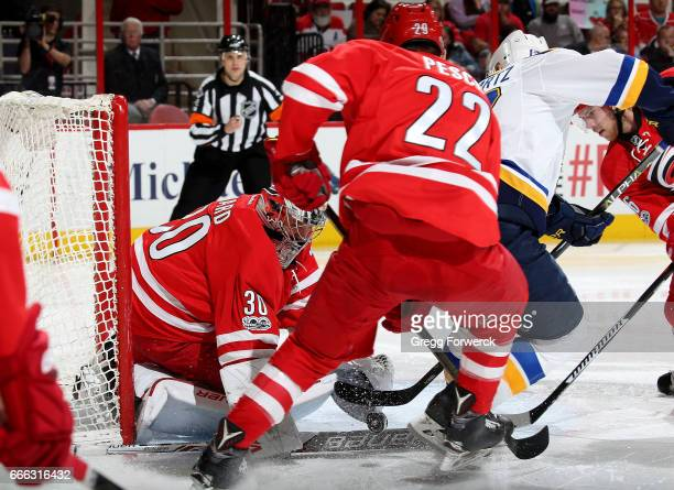 Cam Ward of the Carolina Hurricanes goes down in the crease to cover a puck as teammate Brett Pesce defends and Jaden Schwartz of the St Louis Blues...