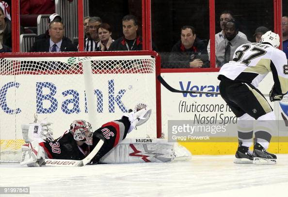 Cam Ward of the Carolina Hurricanes goes into the splits to make a save as Sidney Crosby of the Pittsburgh Penguins backhands the puck wide during a...