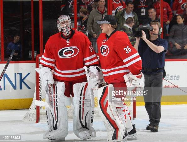Cam Ward of the Carolina Hurricanes is congratulated by teammate Justin Peters after defeating the San Jose Sharks following their NHL game at PNC...