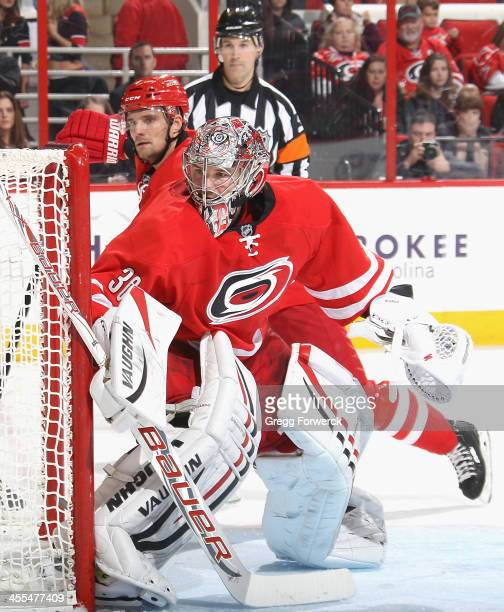 Cam Ward of the Carolina Hurricanes keeps his eye on the puck as he crouches in the crease to protect the net during their NHL game against the San...
