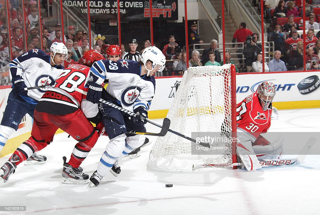 <a gi-track='captionPersonalityLinkClicked' href=/galleries/search?phrase=Cam+Ward&family=editorial&specificpeople=453216 ng-click='$event.stopPropagation()'>Cam Ward</a> #30 of the Carolina Hurricanes keeps his eye on the puck as <a gi-track='captionPersonalityLinkClicked' href=/galleries/search?phrase=Tobias+Enstrom&family=editorial&specificpeople=2538468 ng-click='$event.stopPropagation()'>Tobias Enstrom</a> #39 of the Winnipeg Jets brings the puck around the back of the net during an NHL game on March 30, 2012 at PNC Arena in Raleigh, North Carolina.