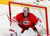 Cam Ward of the Carolina Hurricanes keeps his eye on the puck during an NHL game against the Calgary Flames at PNC Arena on November 10 2014 in...