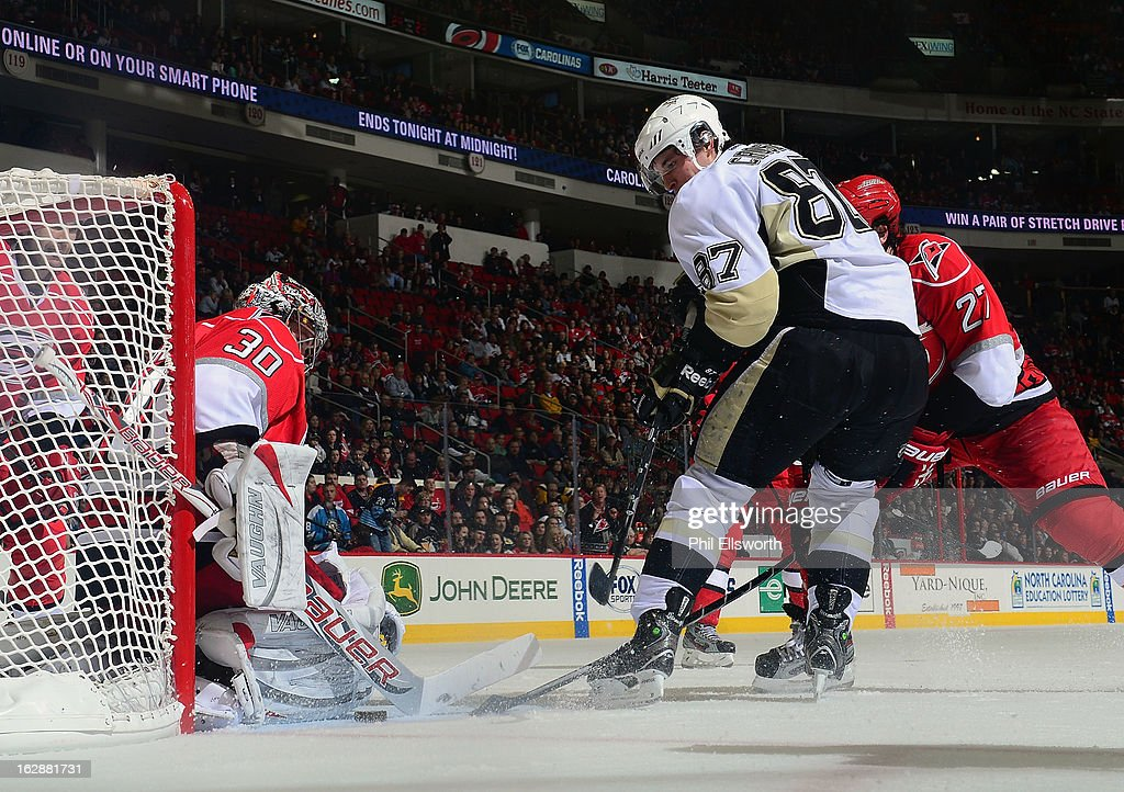 Cam Ward #30 of the Carolina Hurricanes keeps tight against the post to keep an attacking Sidney Crosby #87 of the Pittsburgh Penguins a chance at a goal during an NHL game on February 28, 2013 at PNC Arena in Raleigh, North Carolina.