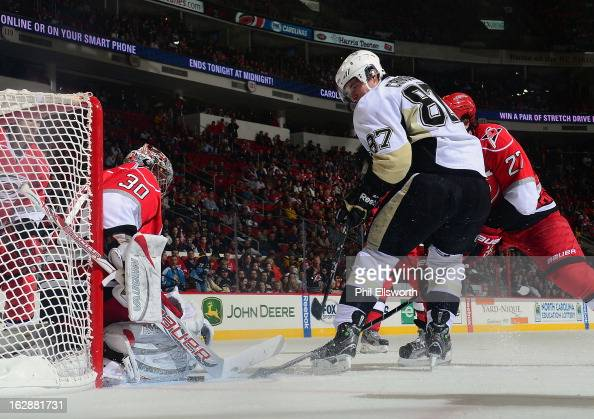 Cam Ward of the Carolina Hurricanes keeps tight against the post to keep an attacking Sidney Crosby of the Pittsburgh Penguins a chance at a goal...