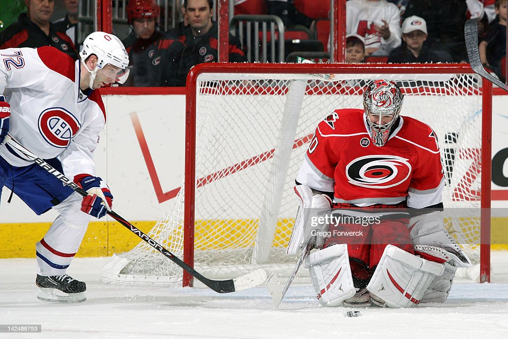 <a gi-track='captionPersonalityLinkClicked' href=/galleries/search?phrase=Cam+Ward&family=editorial&specificpeople=453216 ng-click='$event.stopPropagation()'>Cam Ward</a> #30 of the Carolina Hurricanes looks at a rebounded puck as <a gi-track='captionPersonalityLinkClicked' href=/galleries/search?phrase=Erik+Cole&family=editorial&specificpeople=204754 ng-click='$event.stopPropagation()'>Erik Cole</a> #72 of the Montreal Canadiens closes in on the crease during an NHL game on Apri 5, 2012 at PNC Arena in Raleigh, North Carolina.