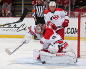 Cam Ward of the Carolina Hurricanes makes a leg pad save next to teammate Mike Komisarek against the Detroit Red Wings during an NHL game on April 11...
